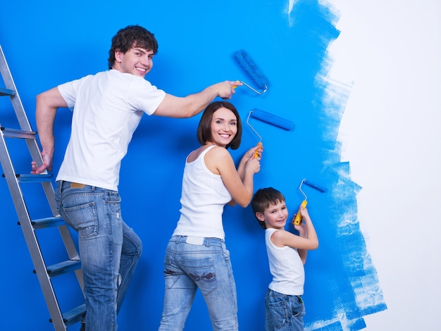 Familia joven feliz con hijo pequeño pintando la pared