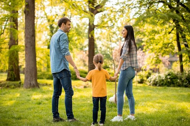 Familia joven feliz con lindo perro bichon en el parque