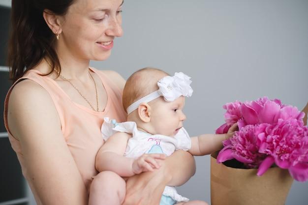 Familia joven feliz mamá y bebé con flores.