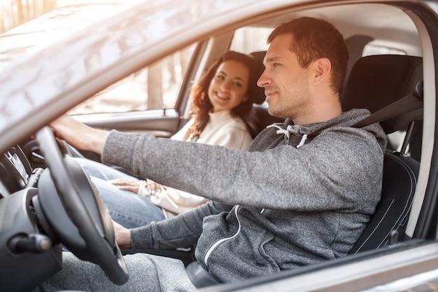 La familia joven feliz monta en un coche en el bosque. un hombre conduce un automóvil y su esposa está sentada cerca. viajando en auto concepto