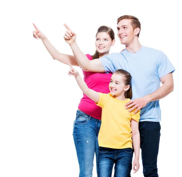 Familia joven feliz con niño apuntando con el dedo hacia arriba - aislado en la pared blanca