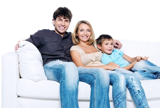 Familia joven feliz con niño emplazamiento en sofá blanco aislado