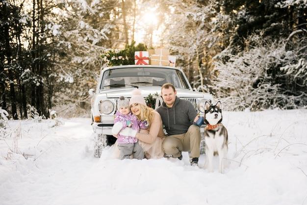 Una familia joven y feliz con un niño pequeño se está preparando para la navidad, caminando con un perro husky en un automóvil retro, en el techo de un árbol de navidad y regalos en el bosque nevado de invierno.