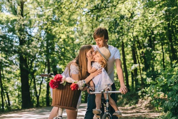Familia joven feliz pasar tiempo juntos afuera. padre madre y su hijo en el parque verde en un picnic.