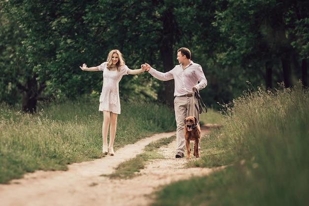 Familia joven feliz en un paseo por el parque de la ciudad. el concepto de felicidad familiar