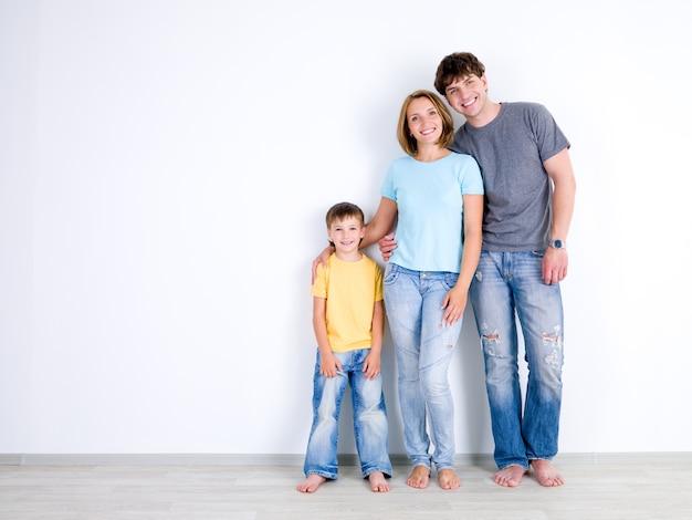 Familia joven feliz con el pequeño hijo de pie juntos en casual cerca de la pared vacía - en el interior