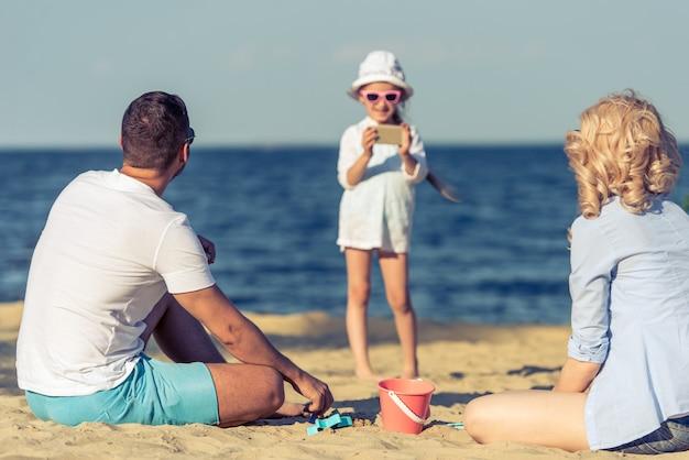 Familia joven feliz en la playa en ver.