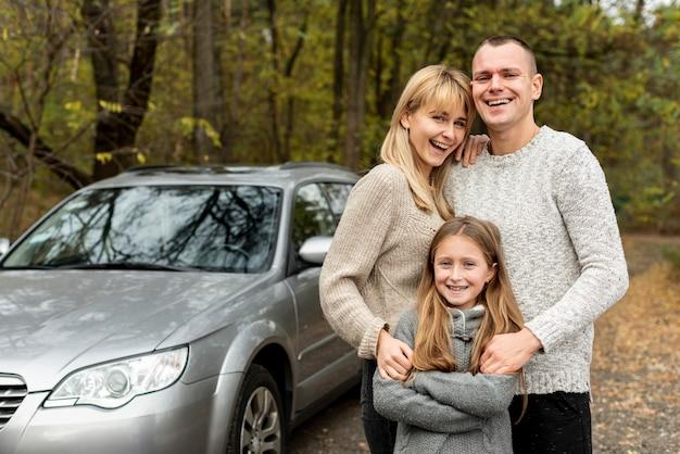 Familia joven feliz posando junto a un automóvil