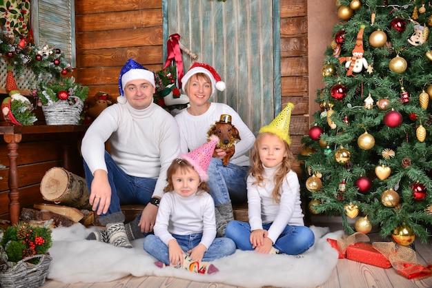Familia joven feliz que se sienta cerca del árbol de navidad con los regalos de navidad.