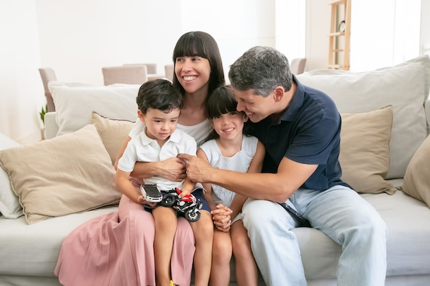 Familia joven feliz sentados juntos en el sofá y sonriendo.