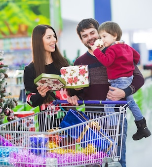 Familia joven feliz en el supermercado elige regalos para el año nuevo.