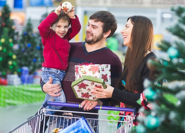 Familia joven feliz en el supermercado elige regalos para navidades