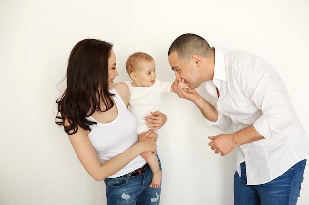 Familia joven hermosa feliz con bebé sonriente abrazando posando sobre pared blanca.