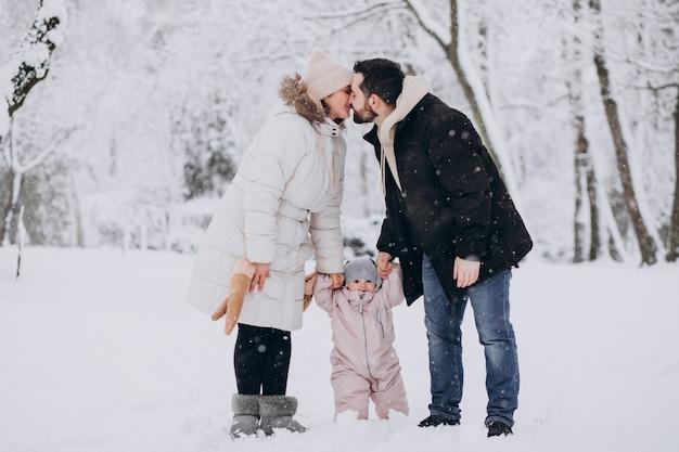 Familia joven con hija pequeña en un bosque de invierno lleno de nieve