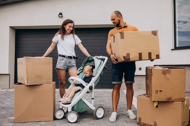 Familia joven con hija pequeña mudarse a casa nueva