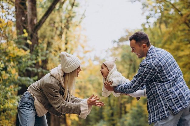 Familia joven con hija pequeña en el parque otoño