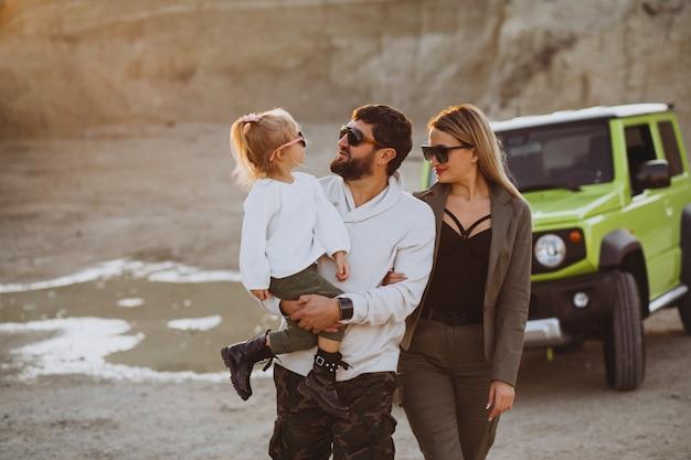 Familia joven con hija pequeña viajando en coche