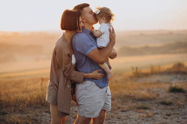 Familia joven con hija en la puesta de sol en un campo