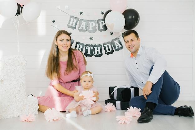 Familia joven con una hija sentada en el suelo y sonriendo