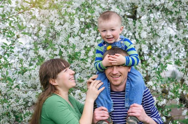 Familia joven con hijo en un floreciente jardín de primavera