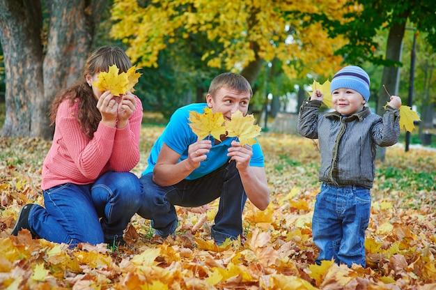 Familia joven con hijo jugando en el parque otoño