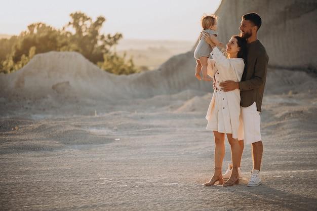 Familia joven con hijo pequeño en la puesta de sol