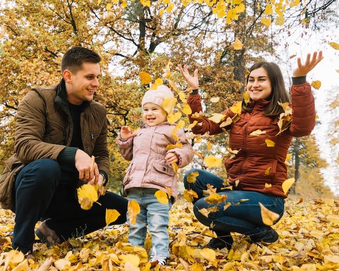 Familia joven jugando con hojas en el bosque de otoño