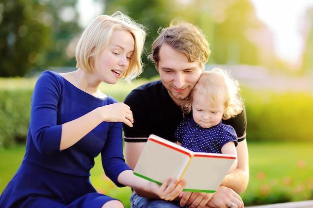 Familia joven leyendo libro de papel juntos al aire libre