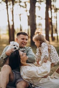 Familia joven con linda hijita descansando en el bosque en la puesta de sol