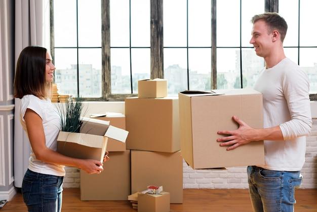 Familia joven llevando cajas de cartón