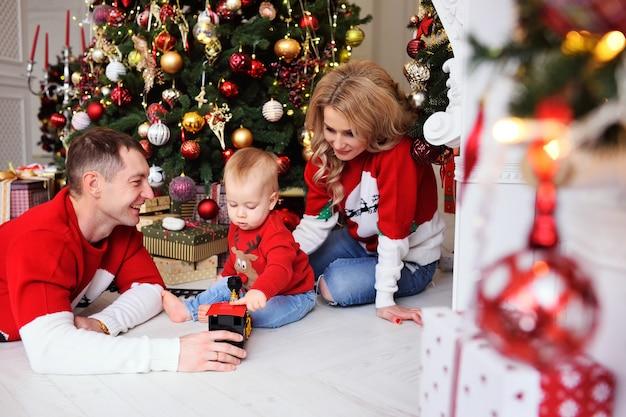 Una familia joven: mamá, papá y bebé jugando y divirtiéndose, árbol de navidad y decoración.