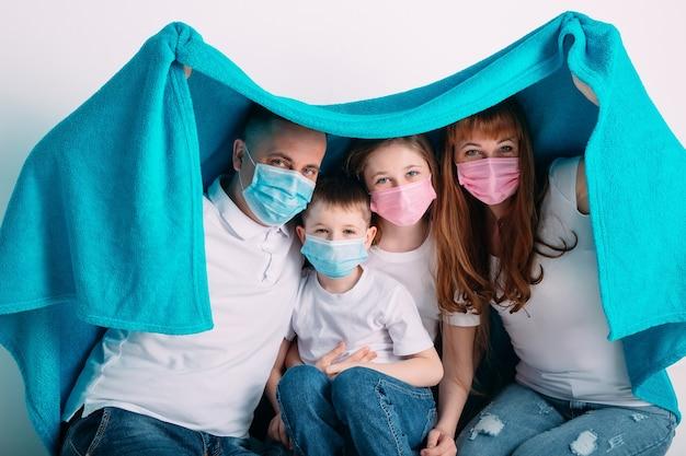 Familia joven en máscaras médicas durante la cuarentena domiciliaria.