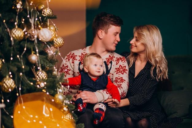 Familia joven con niña sentada junto a árbol de navidad