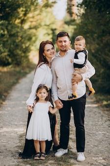 Familia joven con niños en el bosque juntos