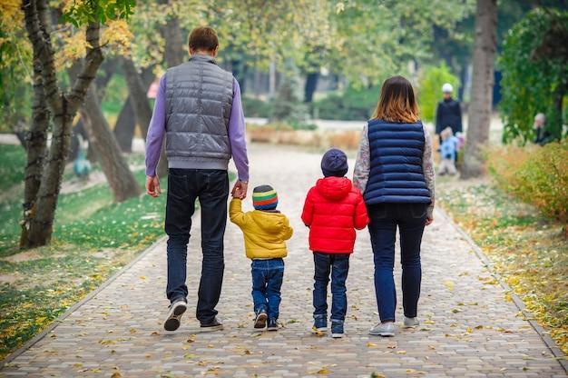 Familia joven con niños camina en el parque