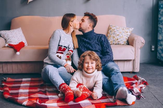 Familia joven padre, madre e hijo vestidos con suéteres de navidad están sentados junto al sofá en una habitación acogedora. el hijo yace entre los padres mira en el marco y sonríe, en el beso de los padres.