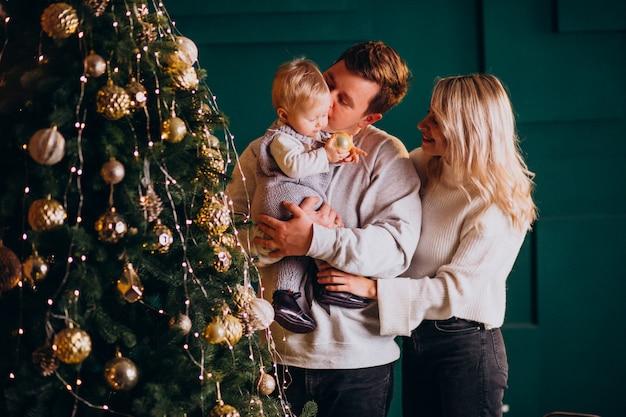 Familia joven con pequeña hija colgando juguetes en el árbol de navidad