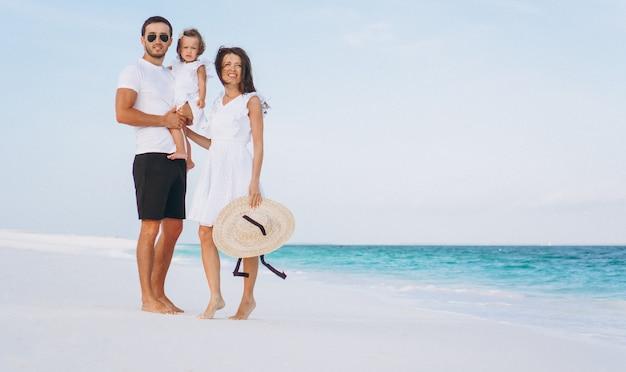 Familia joven con pequeña hija en vacaciones junto al mar