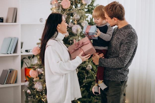 Familia joven con pequeño hijo por árbol de navidad