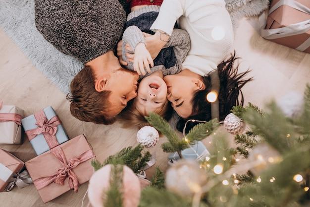 Familia joven con pequeño hijo bajo el árbol de navidad