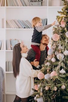Familia joven con pequeño hijo decorar árbol de navidad