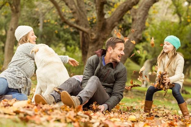Familia joven con un perro en hojas