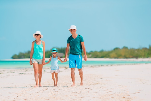 Familia joven en la playa blanca durante las vacaciones de verano