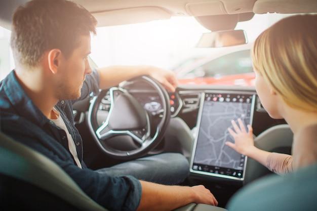 Familia joven que compra el primer coche eléctrico en la sala de exposición. pareja atractiva eligiendo una forma en el tablero electrónico en un vehículo híbrido eléctrico moderno antes de la prueba de conducción.
