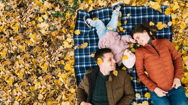 Familia joven que miente en follaje otoñal en el parque