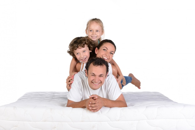 Familia joven que miente junto en el colchón y la presentación.