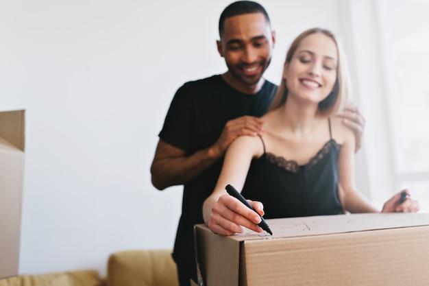 Familia joven que se muda a casa nueva, compra apartamento, piso. cajas de embalaje de pareja alegre con libros, etiquetas de escritura. ellos en la habitación blanca con ventana, vistiendo camiseta negra y camiseta.