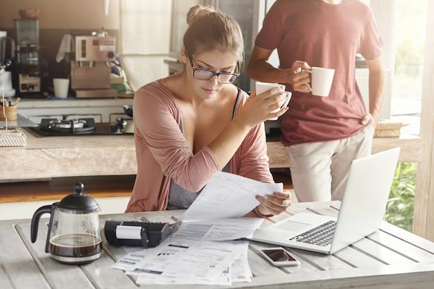 Familia joven que trata asuntos financieros. grave esposa en espectáculos sentado frente a la computadora portátil, mirando a través de facturas, sosteniendo la taza