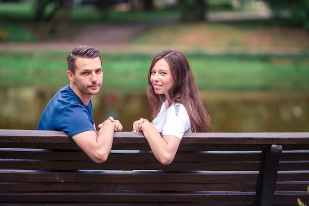 Familia joven relajada en el banco en el parque