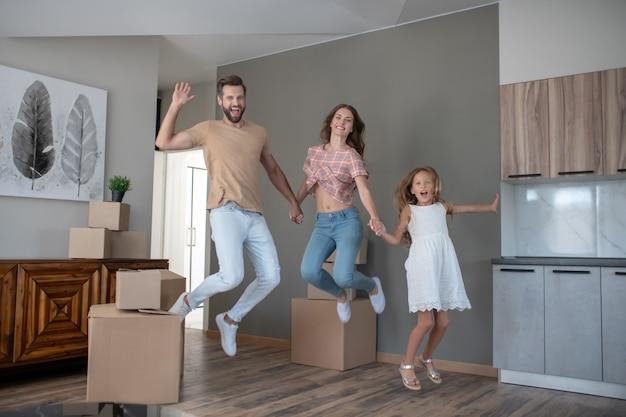 Familia joven saltando y mirando emocionado